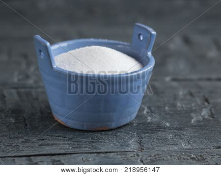 Sea salt fine grind the shaker blue on a rustic table. Natural sea salt is bright white.