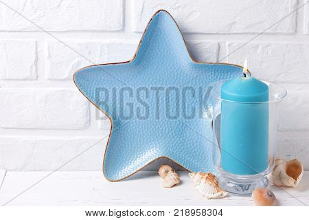 Blue burning candle shells and decorative plate in form of sea starsea star near by white brick wall. Selective focus. Place for text.