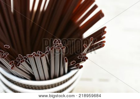 A top view image of several brown plastic stir sticks in a disposable coffee cup.