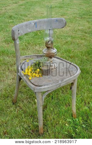 Vintage kerosene lamp glass beaker bouquet of flowers and old chair on the lawn
