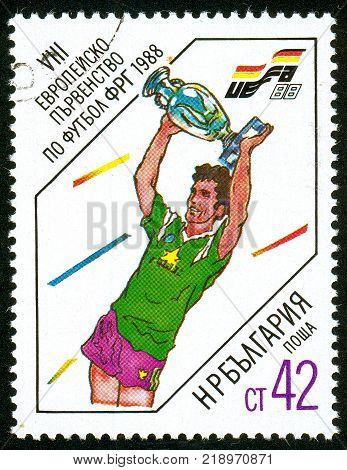 UKRAINE - circa 2017: A postage stamp printed in Bulgaria shows Footballer with uefa cup Series European Football Championship circa 1988