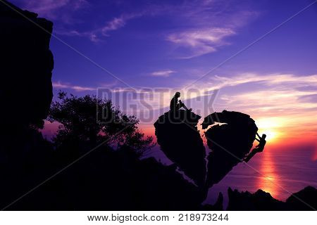 Women and man on broken heart-shaped stone on a mountain with purple sky sunset background.Silhouette Valentine background concept.