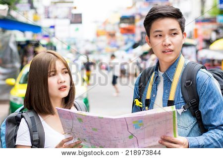 Young couple Asian tourist backpacker getting lost and looking for direction while traveling in Khao San road Bangkok Thailand