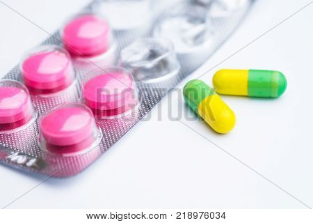 Yellow and green capsule with used magenta tablets medical pills in silver foil pack on white background.