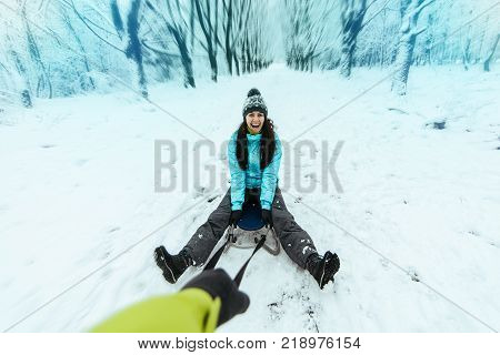 man pull woman on the sled in cold winter day