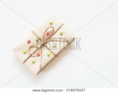 A present or gift box wrapped by rough brown recycled paper and tied with brown hemp rope as ribbon with red and green star isolated on white background with concept of green and environment friendly