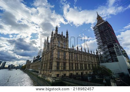 London / UK - 14 November 2017 - Parliament and Big Ben under renovation with cloudy blue sky in winter
