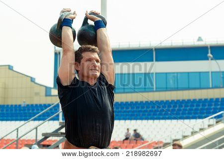 Yoshkar-Ola, Russia - Jule 23, 2016 A participant in city kettlebell competitions performs an approach with two projectiles