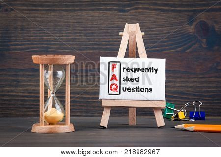 frequently asked questions. Sandglass, hourglass or egg timer on wooden table showing the last second or last minute or time out