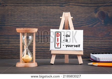 DIY do it yourself. Sandglass, hourglass or egg timer on wooden table showing the last second or last minute or time out