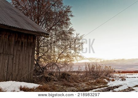 The sun sets behind an old barn house at the rural Finland.