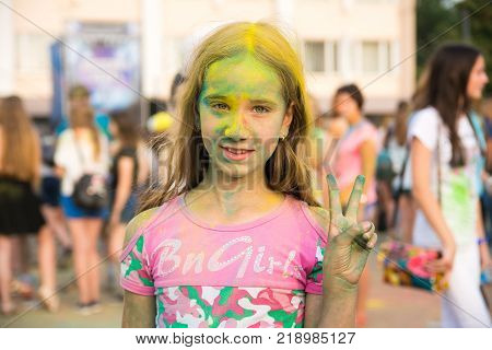 Yoshkar-Ola, Russia - Jule 16, 2016 Happy girl during a paint festival in the central square in Yoshkar-Ola, Russia