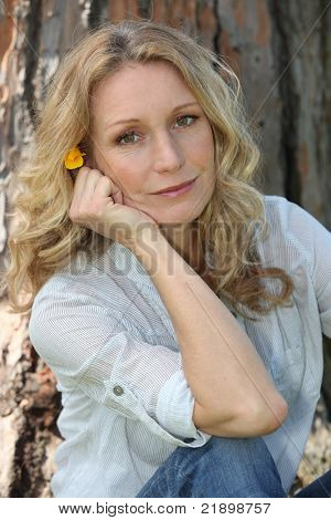 Close-up of woman with flower in hair sitting in front of tree