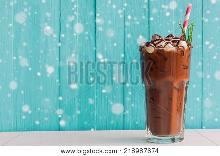 Homemade iced chocolate or cacao in glass topped with marshmallow and chocolate sauce. Delicious iced cacao or chocolate on white wood table and blue background with snowfall. Iced chocolate in bitter sweet and delicious drink concept for holiday.