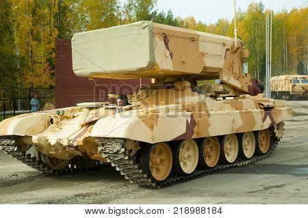 Nizhniy Tagil, Russia - September 26. 2013: Visitors examine military equipment on exhibition range. TOS-1A system fighting vehicle SAolncepek in motion. Russia Arms Expo-2013 exhibition