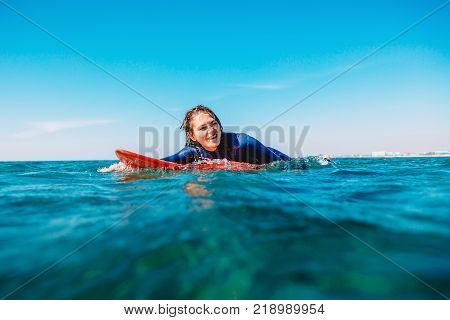Sporty surf girl is smiling and rowing on surfboard. Woman with surfboard in ocean.
