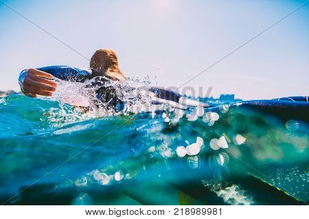 Surf girl on the surfboard. Woman with surfboard in ocean during surfing.