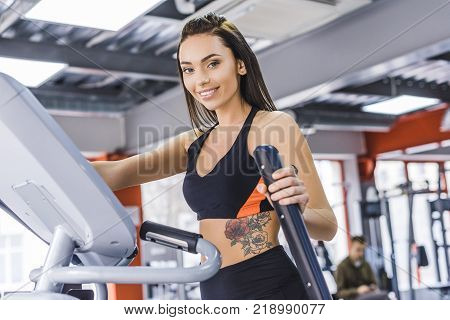 young sportive woman working out on elliptical machine at gym