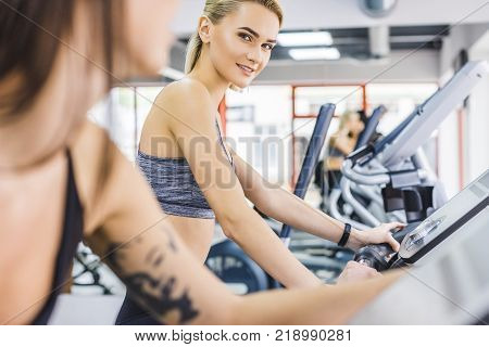 close-up shot of sportive women working out on elliptical machines at gym