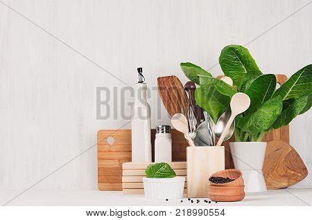 Kitchen modern decor - beige wooden utensils brown cutting boards green plant on soft light white wood background.
