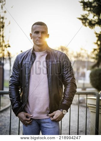 One handsome young man in urban setting in European city, standing, wearing black leather jacket and jeans