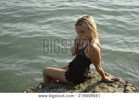 Young beautiful bright seductive blonde girl in a sweeming suit sitting on a stone slab, his legs dangling in the sea, one hand touching the face of a clear Sunny day