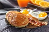 Plate with yummy pancakes, fried bacon and eggs on wooden table poster