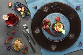 Exquisite restaurant mousse dessert. Chocolate and vanilla souffle on walnut biscuit served at gray table on glass plate finely decorated with fresh berries and mint. Haute cuisine concept, top view poster