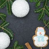 A festive frame of spruce branches, white fluffy gleaming balls, a gingerbread snowman and cinnamon sticks.Dark concrete Christmas or New Year background. Top view.Close up. Square crop poster