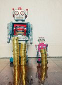 concept inequality wit two vintage robot toys on a wooden floor with reflection  poster