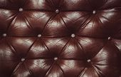 Texture of genuine leather upholstered furniture. Decorative brown background. Decorative background of genuine leather capitone texture poster
