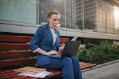 Busy woman is in a hurry, she does not have time, she is going to eat snack outdoors. Worker eating and working with documents on the laptop at the same time. Businesswoman doing multiple tasks. Multitasking business person poster