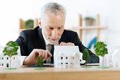 Very attentive. Clever experienced reliable real estate agent sitting in his office and looking attentively at the model of a wonderful house in the countryside while planning how to sell it poster