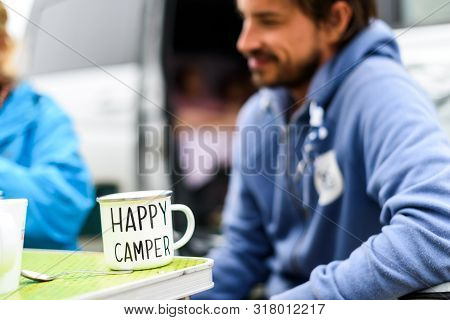 Man Camping Travelling With Breakfast Mug And Happy Camper Text. Man Drinking Coffee Or Tea From Spe
