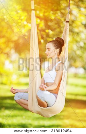 Anti-gravity Yoga outdoor. Happy woman doing yoga exercises, meditate in sunny park. Yoga meditation in hammock. Concept of healthy lifestyle and relaxation. Pretty woman relax at yoga hammock