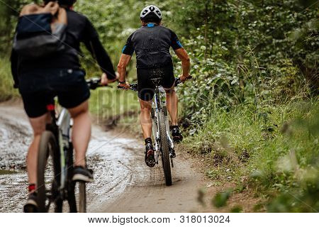 Back Two Cyclists Riding Mountain Bike On Dirty Trail In Forest