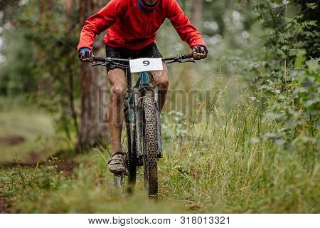 Dirty Athlete Cyclist On Mountainbike Riding Uphill In Forest Trail