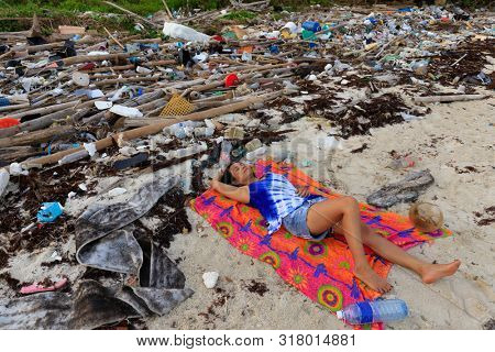 Woman lying on a beach with important plastic pollution in Thailand