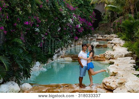Couple Smiling. Multiracial Couple Hugging. Couple On Vacation. Multiethnic Couple At The Swimming P