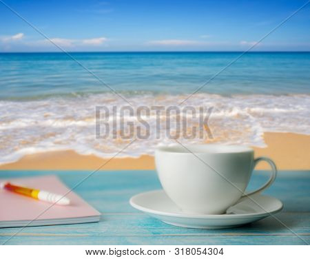 A Cup Of Coffee And Notebook With Blurred Beach Sand And Blue Sky In Day Light, Relax And Remember C