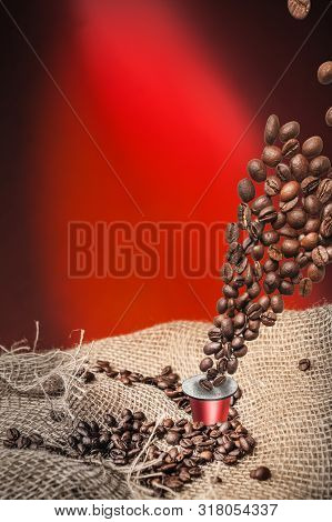 Coffee Capsule And Coffee Beans On Dark Red Background