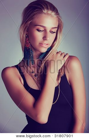 beautiful young blond woman with long hair wearing long feather coral earrings - shot as low key portrait with retro effect.