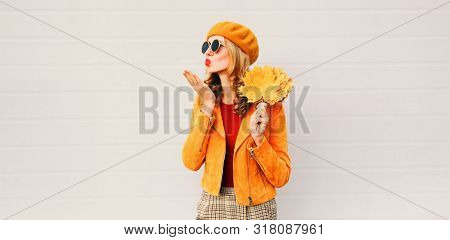 Autumn Mood! Woman With Yellow Maple Leaves Blowing Red Lips Sending Sweet Air Kiss Over Gray Wall B