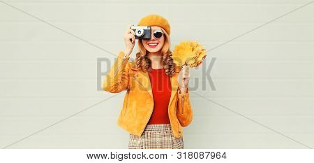Happy Smiling Woman With Autumn Yellow Maple Leaves, Retro Camera Taking Picture In French Beret Ove