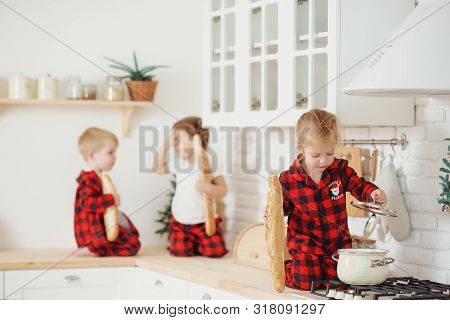 Cute little children in red pajamas, preparing cookies and eats a bred in the kitchen at home. Sits on the kitchen table and helps mom prepare a festive Christmas dinner poster
