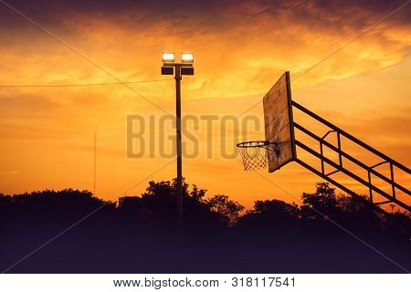 Silhouette Of Outdoor Basketball Court With Dramatic Sky In The Sunrise Morning