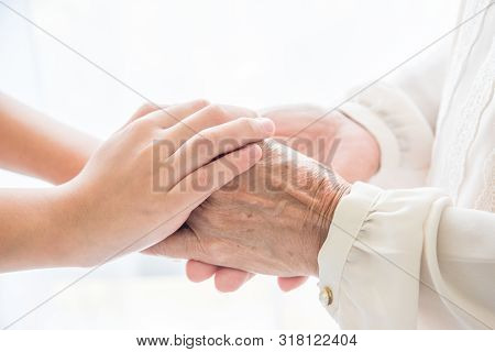 Close Up Of Young Girl Holding Senior Hands ,family Care And Support Concept .