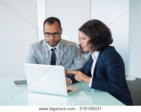 Female Mentor Showing Presentation On Laptop To Intern. Business Man And Woman Sitting At Computer A