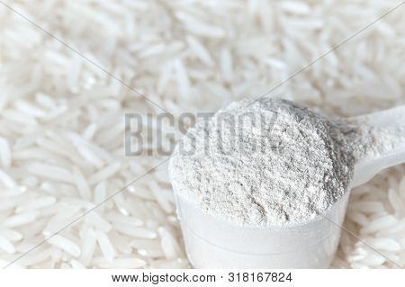 Rice Protein Powder In A Measuring Spoon.