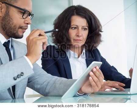 Business Colleagues Analyzing Digital Reports On Tablet And Laptop. Business Man And Woman Sitting A